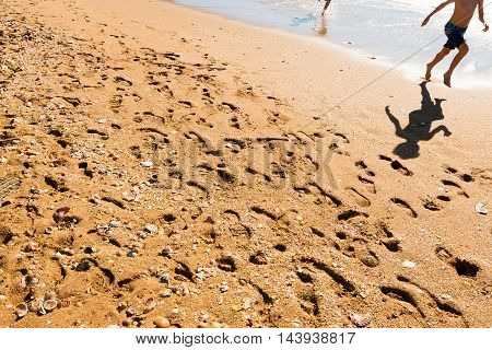Two unrecognizable happy kids jumping on the beach with reflections in great sunlight