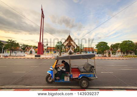 BANGKOK - SEPTEMBER 21: Male name does not appear reading the newspaper Reading on Thai Tuk Tuk taxi Parked in front Giant swing and Wat Suthat Temple September 21 2014 in Bangkok Thailand.