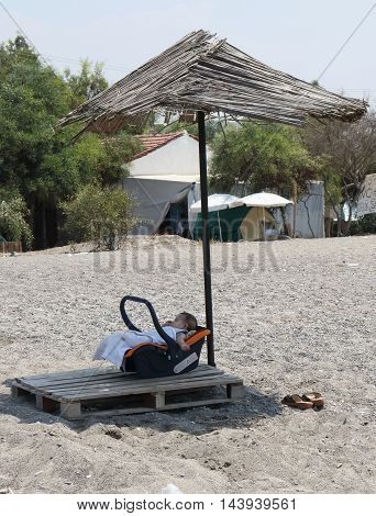 31ST JULY 2016,CALIS,TURKEY: A young baby in the shade on calis beach in turkey, 31st july 2016