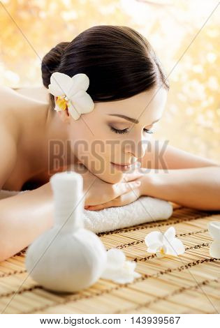 Young and beautiful girl relaxing in spa salon. Massage therapy over seasonal autumn background. Healing medicine and health care concept.