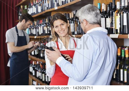 Saleswoman Showing Wine Bottle To Customer In Supermarket
