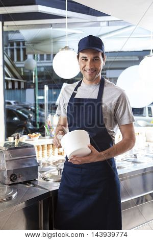 Smiling Worker Holding Bowl At Ice Cream Parlor