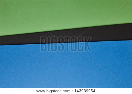 Colored cardboards background in blue black green tone. Copy space. Horizontal