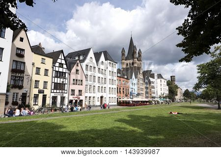 Cologne, Germany - August 20, 2016: Facades of historic buildings cafes and restaurants in the historic town center of Cologne Germany. Some tourists and passersby on the street. In the background romanesque church Gross Sankt Martin