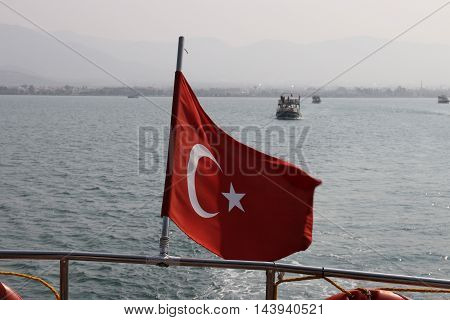 A turkish flag flying on the stern of a boat in turkey