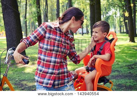 Mom takes tender care of her son while riding a bike. They enjoying a nice summer day in the park