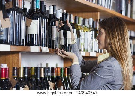 Woman Reading Wine Bottle's Label In Shop