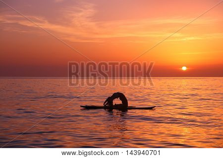 Silhouette of a yoga trainer balancing on the water on the paddle board over beautiful orange sunset background, doing yoga asana Urdhva dhanurasana on the beach