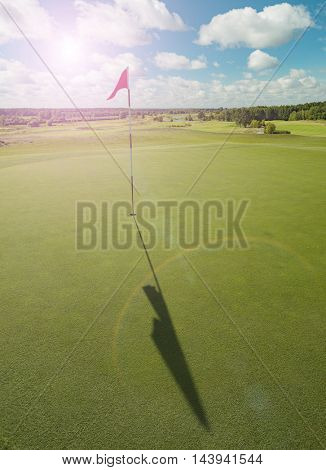 Golf course with red flag and sun flare