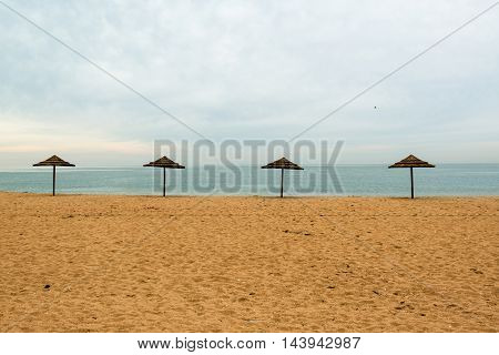 Lonely beach with abandoned umbrellas at the end of the vacation period