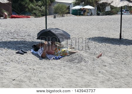 31ST JULY 2016,CALIS, TURKEY; A local turkish man laying in sand under an umbrella and under a second umbrella  along Calis beach in Turkey,31st july 2016