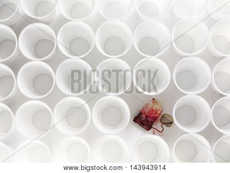 teabag with red hibiscus tea between ordinary rows of white plastic cups abstract clean art concept of social issues such as being different or consequences from staff shortening
