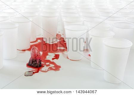 bleeding teabag with red hibiscus tea in front of white plastic cups abstract concept of social issues such as influence exploitation or defense