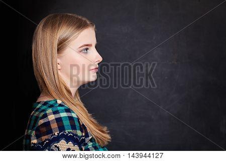 beautiful Cute Girl on Blackboard Background. Profile