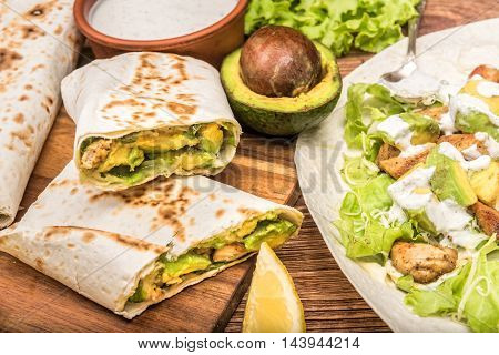 Chicken, avocado and vegetables burrito on the wooden background.