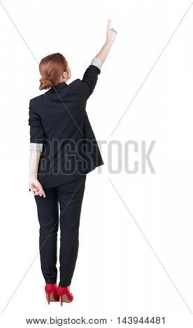 Back view of young redhead business woman pointing at wall. beautiful girl in dark suit. Rear view people collection. backside view of person. Isolated over white background.