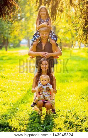 Happy family playing and forming a tower in the park.