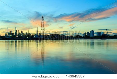 Oil refinery and surrounding communities at twilightChao Phraya river Thailand