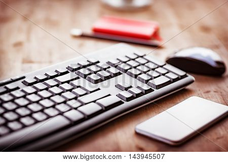 Desktop in the office, computer keyboard, pc mouse and mobile phone on the wooden table, work place