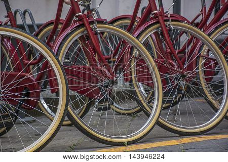 The wheels of the big red bicycles on the street