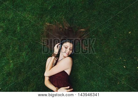 Pretty young girl music lover lying on grass in park, happy and smiling, wearing headphones. Female teenager in earphones closeup portrait. Woman top view