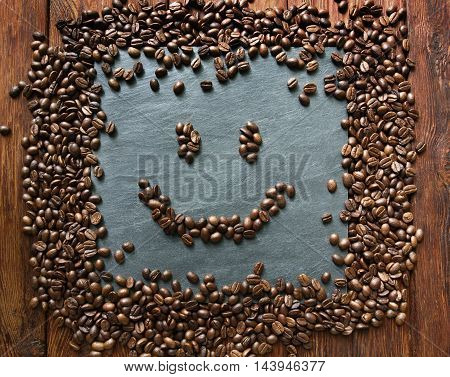 Smiley face from coffee beans. Heap of roasted coffee bean on grey stone surface texture and wooden table. Coffee shop or cafe background. Smiling face from beans. Soft color toning, top view