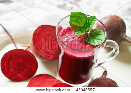 Beetroot juice with mint leaves and beetroots scattered around on white background