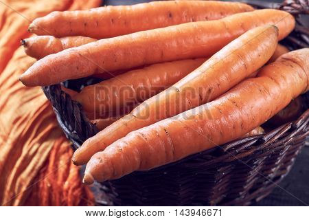 Fresh carrots in woven basket on wooden background