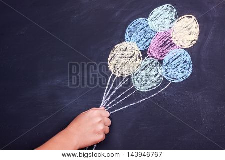 hand holding chalk drawing balloons on a blackboard background