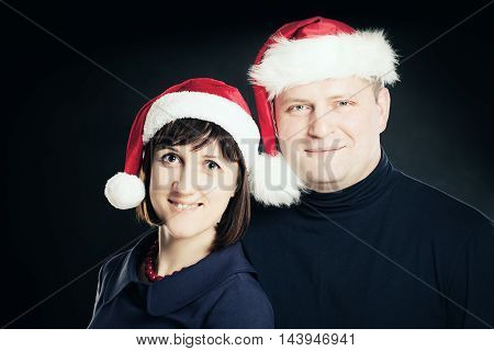 Christmas Couple. Man and Woman in Santa Hat on Blackboard Background