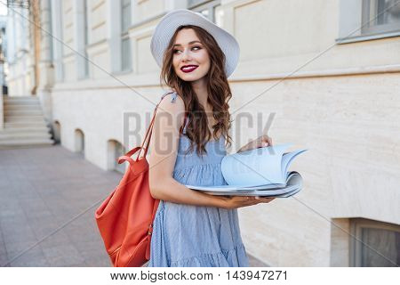 Happy pretty young woman in hat with backpack standing and reading a book on the street