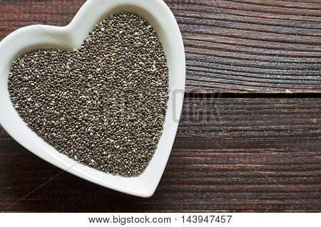 Chia seeds in heart shaped ceramic bowl on wooden background. Top view with copy space