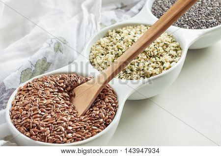 Flax hemp and chia seeds in bowl on white background. Vegan sources of Omega-3
