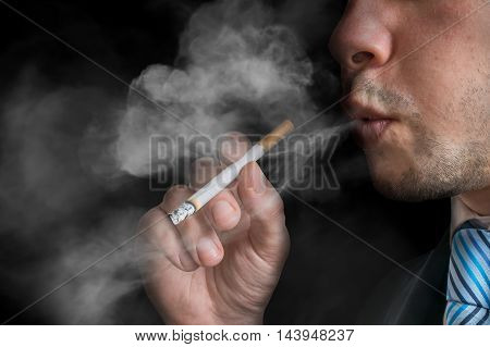 Young Man (smoker) Holds Cigarette And Smoking. A Lot Of Smoke A