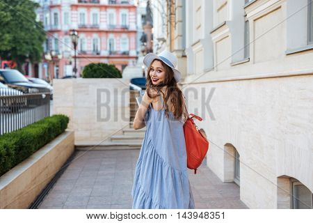 Smiling attractive young woman with backpak and books walking on the street