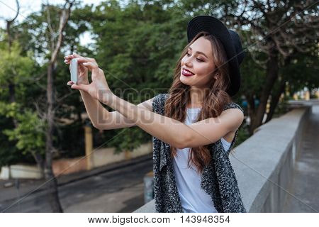 Young beautiful stylish brunette girl making selfie with her phone outdoors