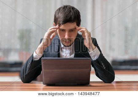 Young intend and thinking businessman working with laptop.