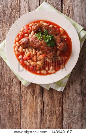 Grilled Sausage With Beans In Tomato Sauce On A Plate Close-up. Vertical Top View