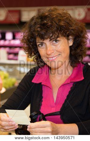 pretty Brunette woman holding receipt in supermarket