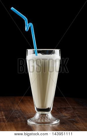 Milk shake (cocktail) with berry and banana in glass on brown wooden table