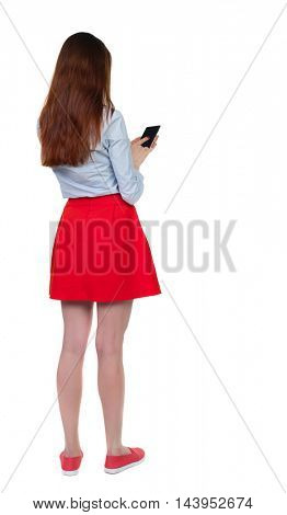 back view of standing young beautiful  woman using a mobile phone or tablet computer. girl  watching. Rear view people collection.  backside view of person.  Isolated over white background. Long