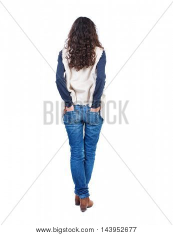 back view of standing young beautiful  woman.  girl  watching. Rear view people collection.  backside view of person. Long-haired girl with curly hair standing with his hands in the back pockets of