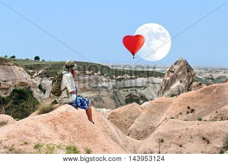 lonely traveler looking Balloon on a background of colored mountains the Cappadocia, Central Anatolia, Turkey