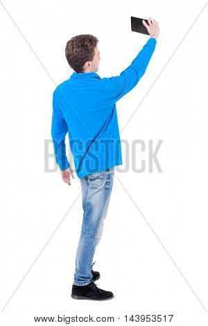 back view of standing business man photographing a phone or tablet. Rear view people collection.  backside view of person.  Isolated over white background. Curly boy in blue sweater makes selfie