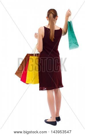 back view of going  woman  with shopping bags . beautiful girl in motion.  backside view of person.  Rear view people collection. Isolated over white background. Slim blonde in a burgundy dress