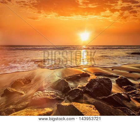 Tropical beach vacation background - waves and rocks on beach on sunset with beautiful cloudscape. With lens flare and light leak