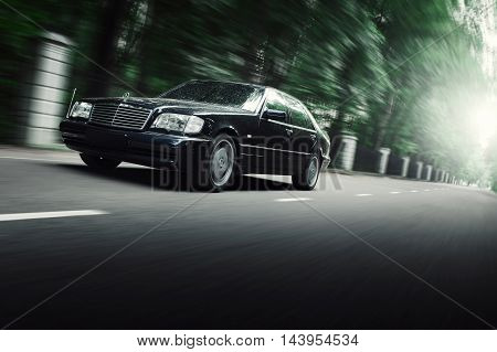 Moscow, Russia - July 25, 2016: Black car Mercedes-Benz S-Class W140 drive on asphalt road in nature park of city Moscow at daytime
