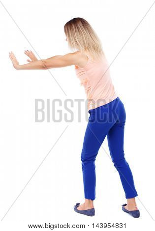 back view of woman pushes wall.  Isolated over white background. Rear view people collection. backside view of person. Blonde in blue pants shoves something with his hands.