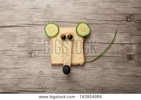 Funny mouse made of bread and cheese on wooden background