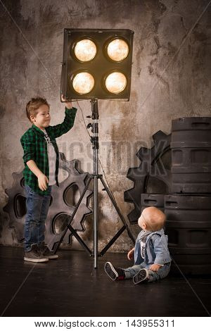 Cute boy in a plaid shirt fixing lights in a photo studio and showing this to his little brother. Lighting correction. Young photographer changing light force. Gears background. Brothers. Siblings.